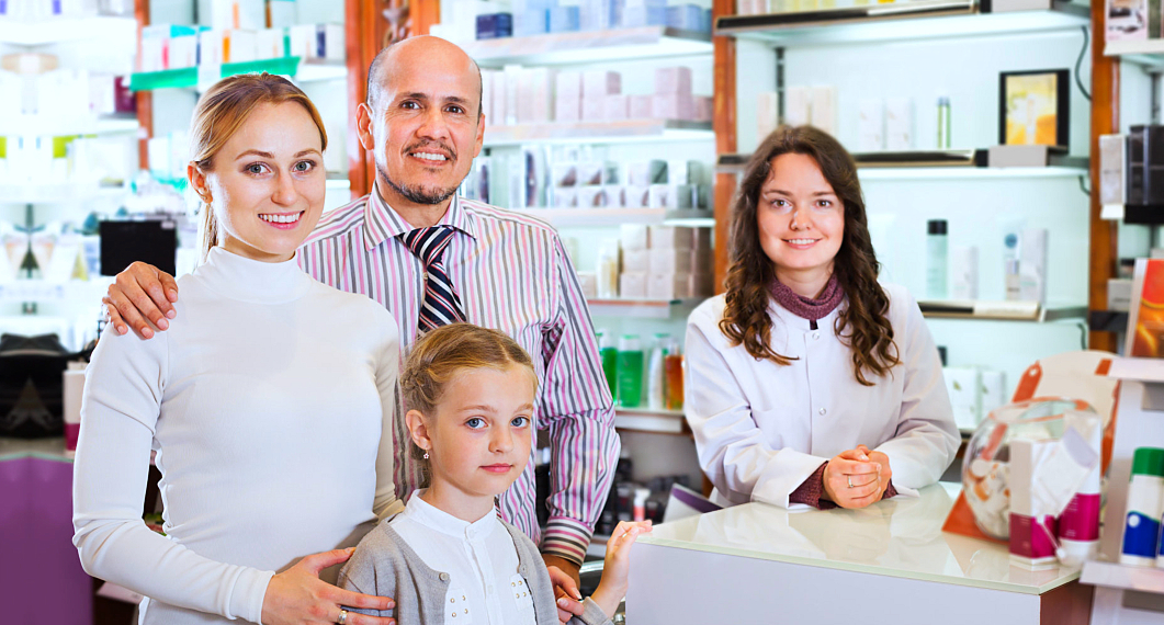 pharmacist and a family smiling