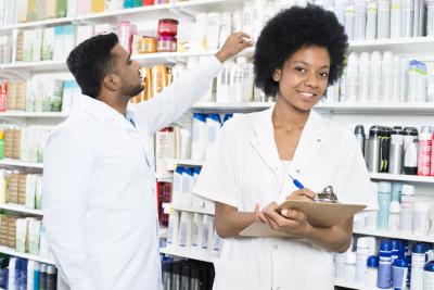 portrait of female pharmacist writing on clipboard